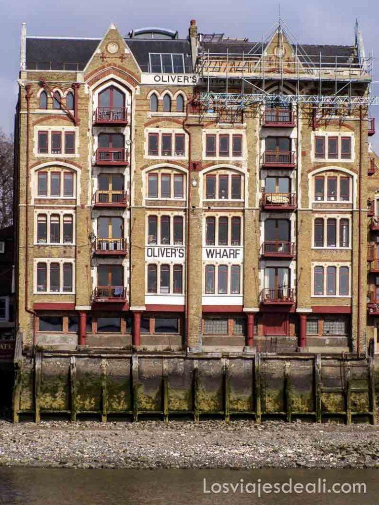 fachada llena de ventanas junto al río edificio de la época de la revolución industrial