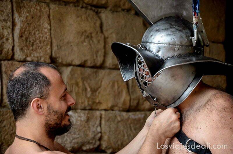 un asistente ata el cordón que sujeta el casco de metal a un guerrero en el festival de tarraco viva
