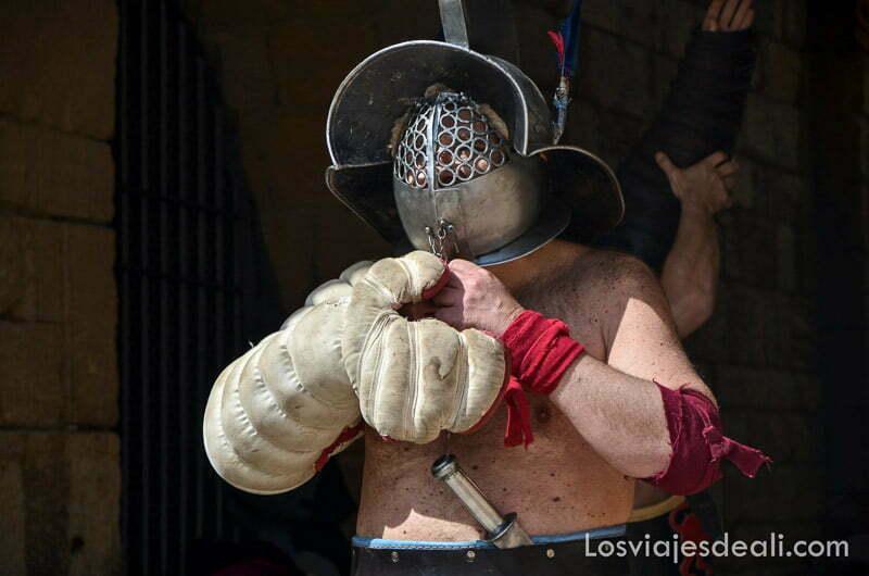 guerrero romano con casco con agujeritos para ver y un guante muy grueso de protección en una mano en el festival de tarraco viva