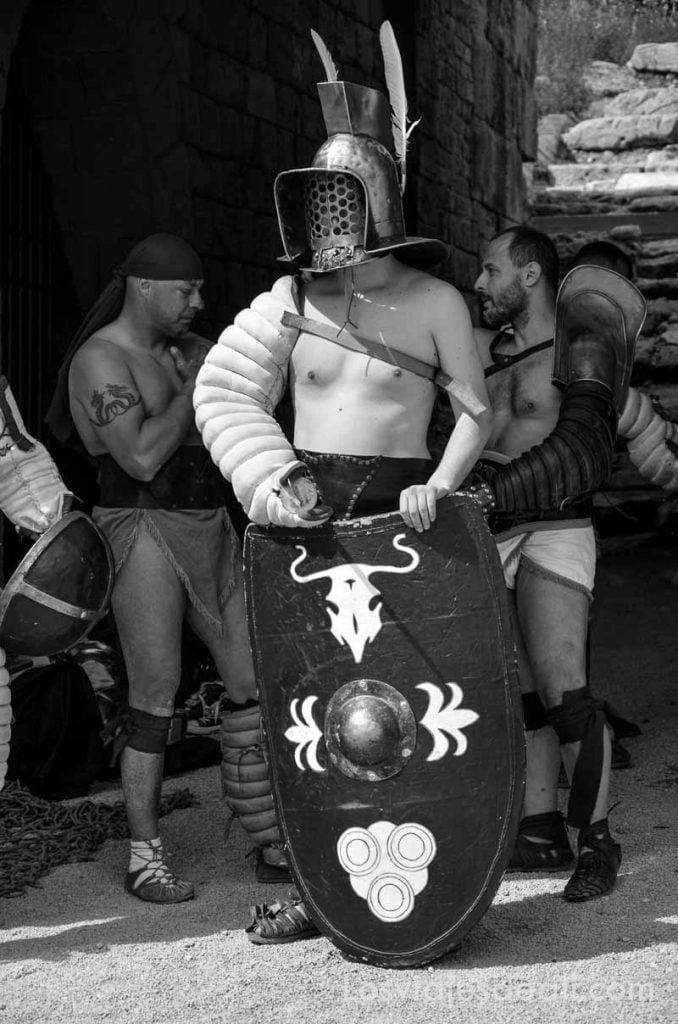 guerrero esperando con su escudo y el pecho descubierto excepto un brazo que lo lleva cubierto con tela acolchada para protegerse
