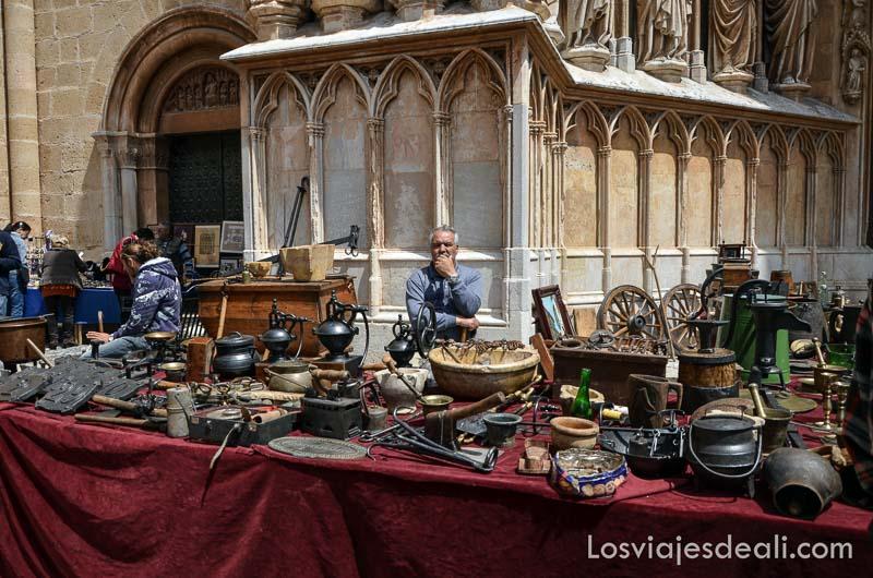puesto del mercadillo de antigüedades de tarragona con muchos objetos distintos