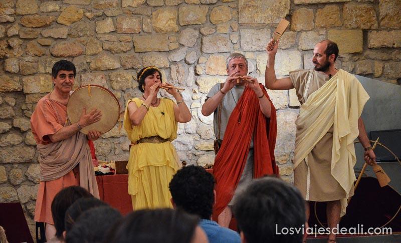 cuatro músicos vestidos como antiguos romanos tocando instrumentos de la época