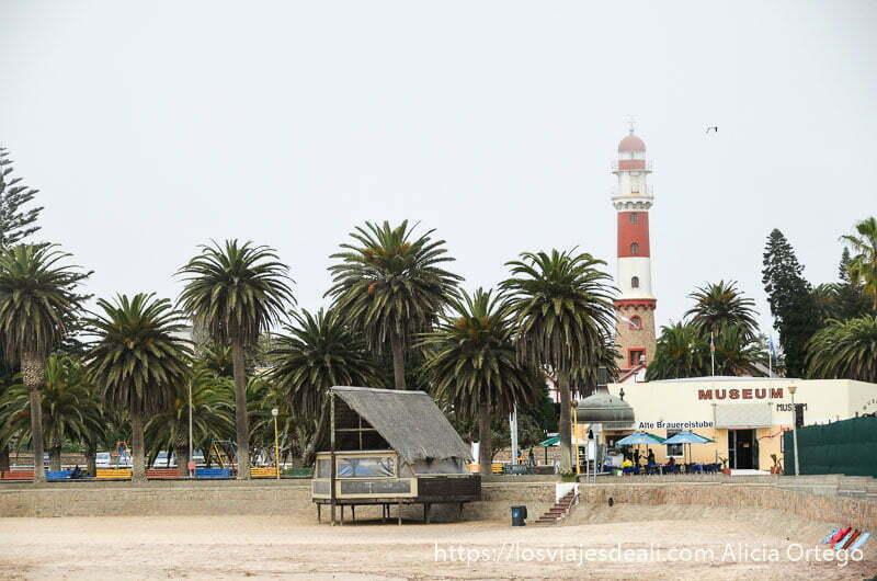 faro de costa pintado de blanco y rojo junto a la playa y una fila de palmeras
