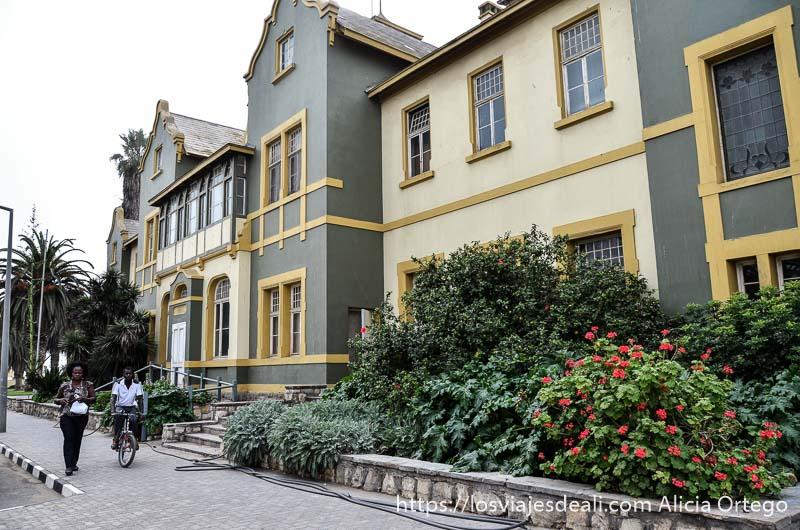 casas de estilo alemán y una pareja negra andando por la acera junto a ellas en swakopmund