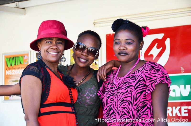 tres africanas modernas con vestidos rojos y rosas, sombreros y gafas de sol, sonriendo a la cámara