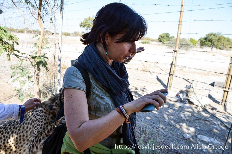 de pie con el guepardo enganchado a la mochila de la espalda