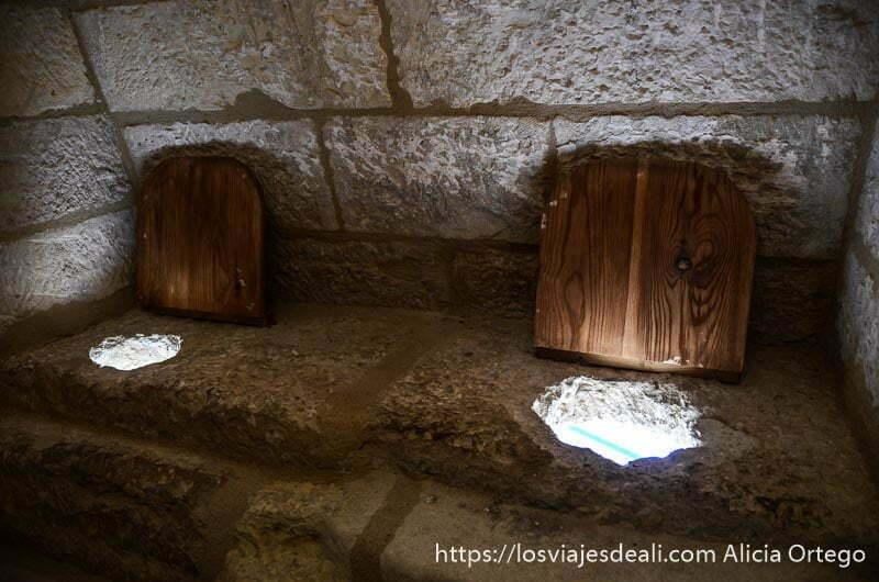 retretes medievales son agujero en asiento de piedra y tapa de madera
