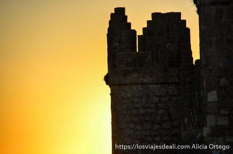 silueta de torre del castillo recortándose en cielo naranja por atardecer