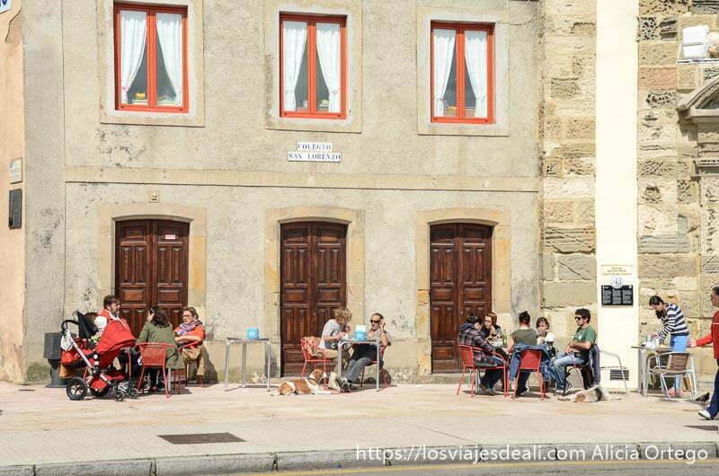 gente sentada en las mesas de una terraza al sol en gijón