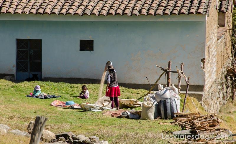 mujer aventando grano tirándolo desde alto junto a su casa