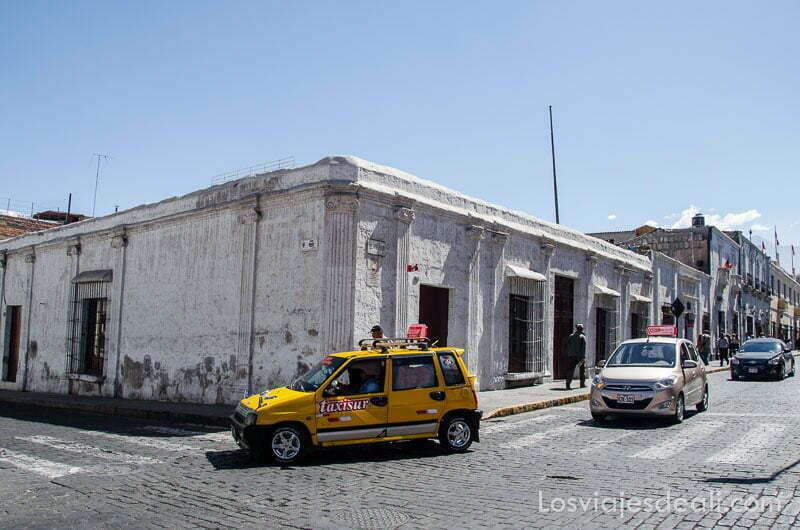 cruce de calles en arequipa con edificios bajos encalados y un taxi amarillo
