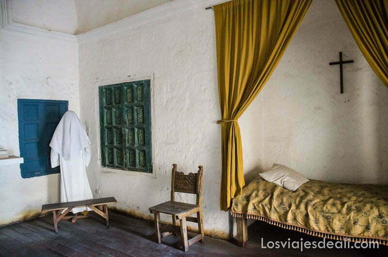 habitación de monja con cama con cortina y silla de enea