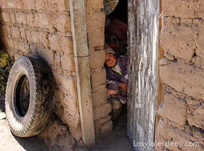 niño pequeñito asomándose por la puerta de chapa de su casa de adobe
