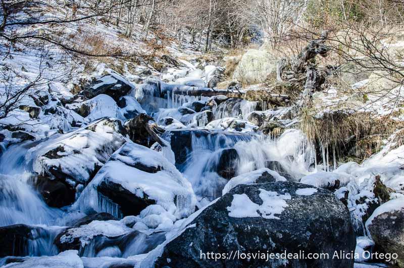 agua cayendo entre rocas con nieve y hielo en el camino de respomuso