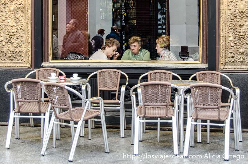 tres señoras merendando en un café vistas a través del cristal con grupo de sillas de terraza delante