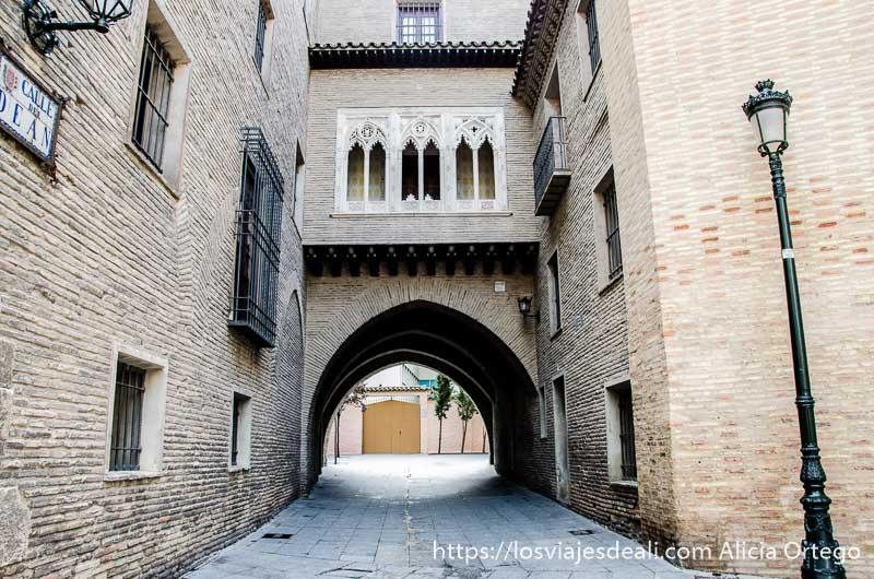 callejón que pasa bajo un arco con farola de hierro a la derecha