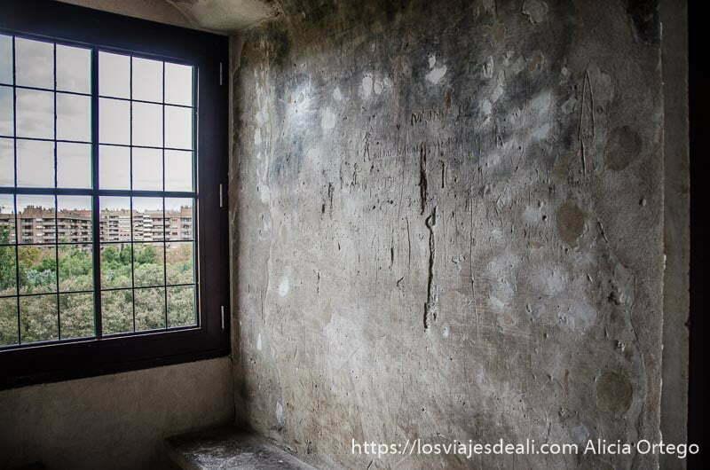 pared de celda de antigua prisión con grafitis de prisioneros y ventana que mira al exterior
