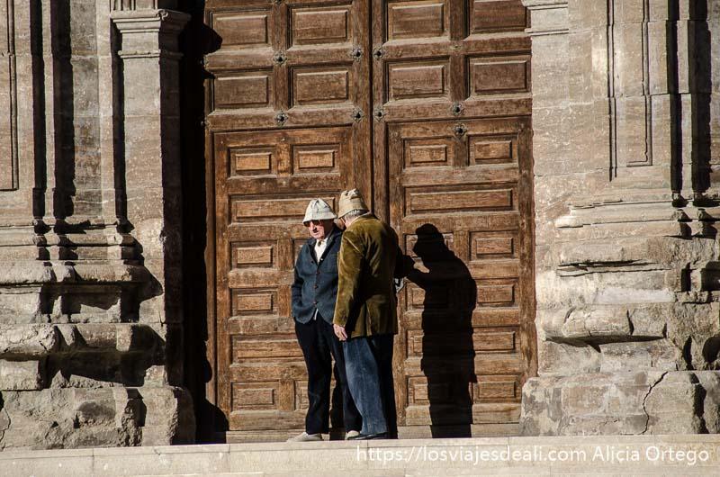 dos ancianos con gorro en la puerta de una iglesia cerrada fin de semana en zaragoza