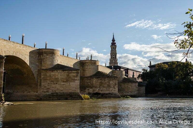 puente sobre el río ebro con torre de iglesia al fondo