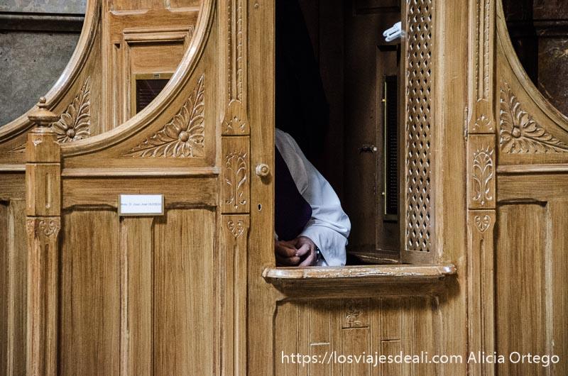 cura dentro de confesionario escuchando confesión
