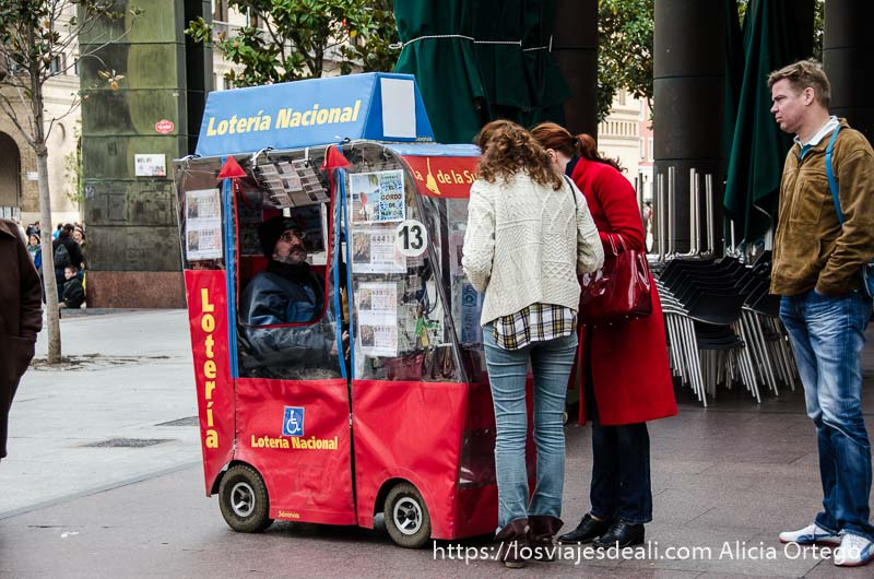 señor vendiendo lotería en un motocarro con dos clientas mirando números