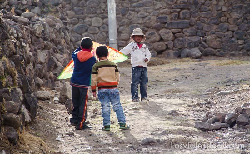 tres niños jugando con una cometa en uno de los pueblos del valle del colca
