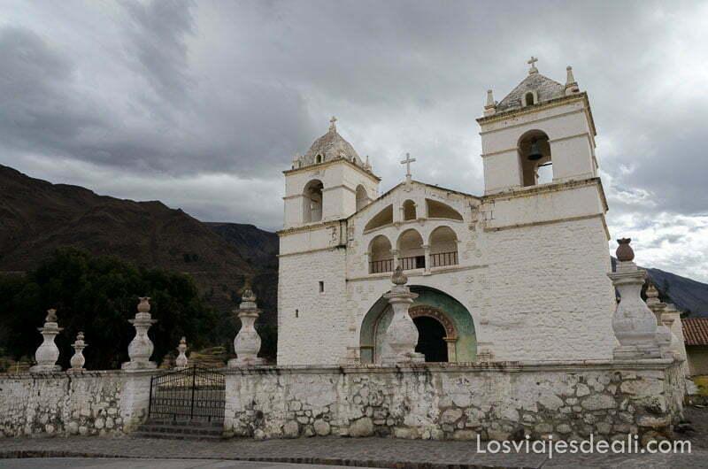 iglesia colonial pintada de blanco bajo cielo con muchas nubes