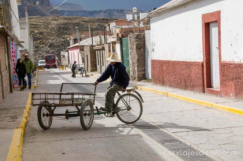 hombre en carrito con bici dando la vuelta en la calle de uno de los pueblos del valle del colca