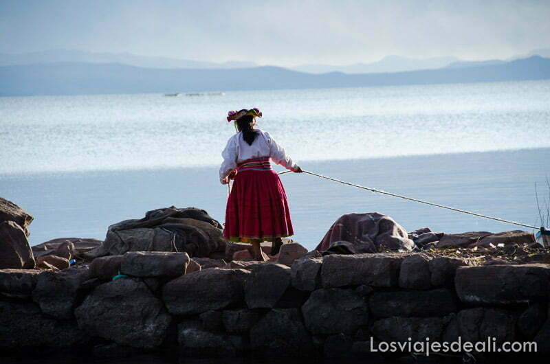mujer tirando de cuerda de barca para amarrarla en el dique junto al titicaca