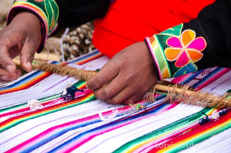 manos de mujer trabajando en un tela con lanas de colores a rayas