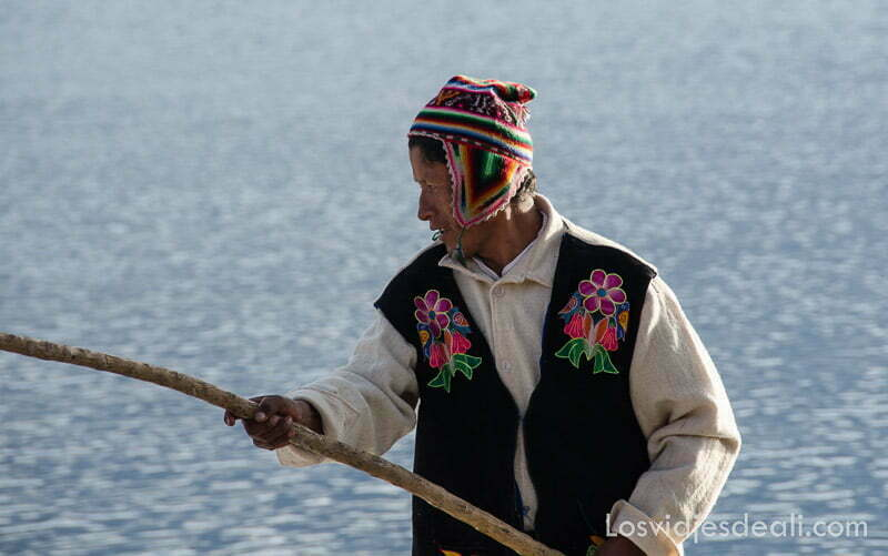 hombre de la península de capachica con chaleco negro y flores bordadas y gorro de lana con orejeras de vivos colores
