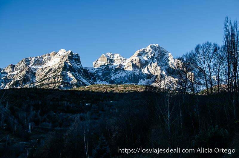 tres picos de montaña con nieve recortándose en el cielo azul