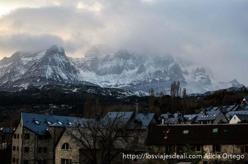 casas de piedra y montañas con nieve semitapadas por nubes al atardecer