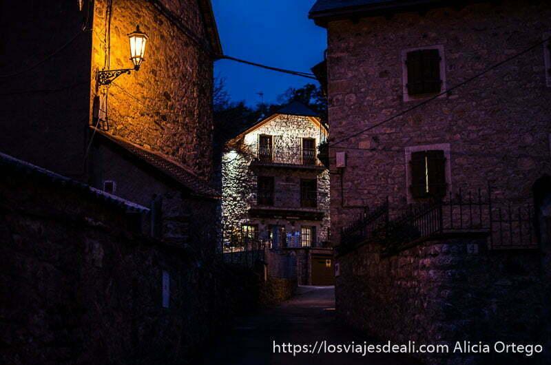 calle con casas de piedra y farolas encendidas en la hora azul