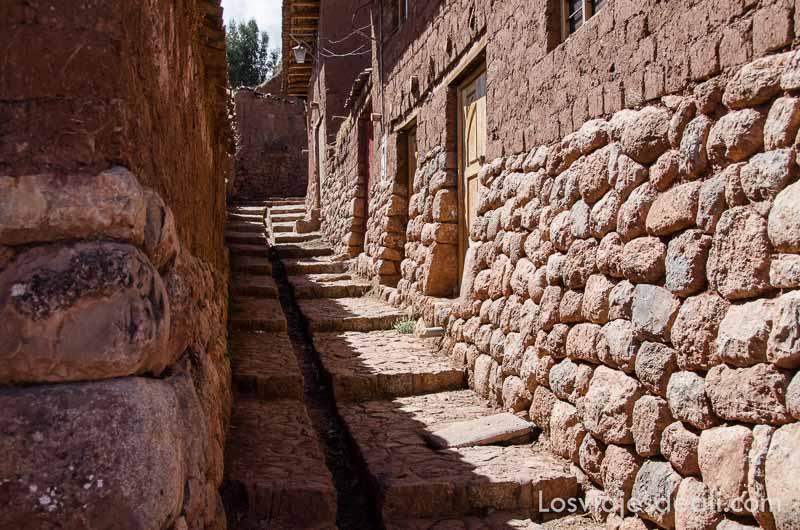 calle con casas de piedra hasta media pared y adoquinado con canal central para que baje el agua