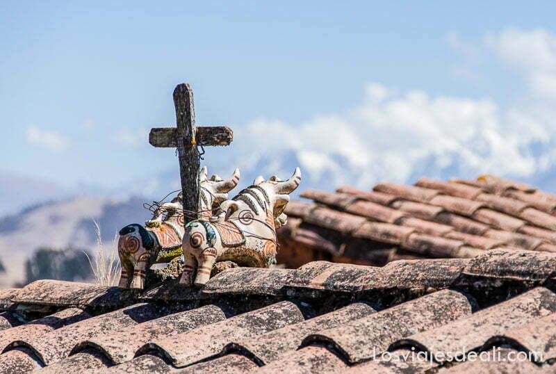 cruz de madera con dos toros de cerámica en un tejado