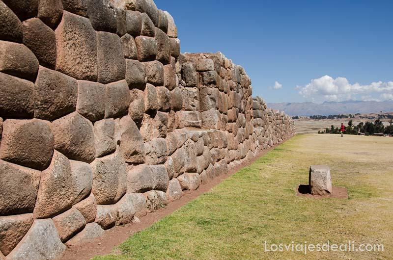 muro inca de piedras junto a campo verde