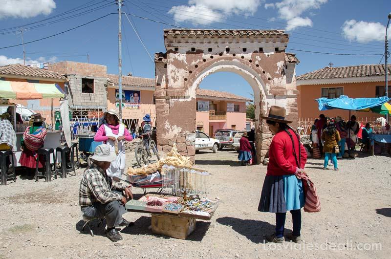 puerta del recinto del mercado con un arco y puesto de chucherías con una india con sombrero falda y trenzas