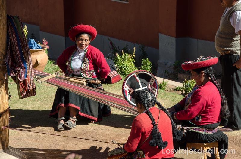 mujeres andinas con sombrero y chaquetilla rojos y pelo muy largo trenzado