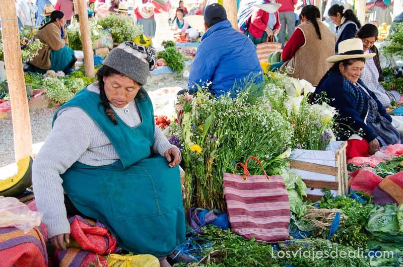 puestos de flores llevados por mujeres sentadas