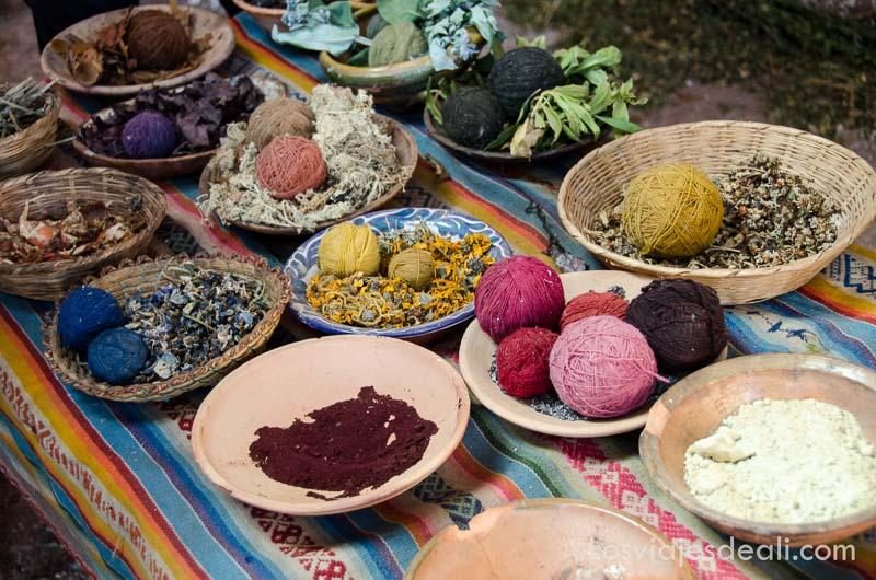 cuencos con ovillos de lanas y hierbas de donde extraen los colores