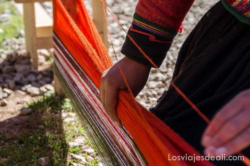 mano de mujer cogiendo lanas de colores tensadas en un telar