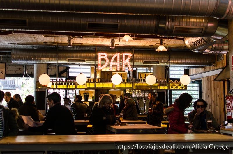 mesas y letrero que pone BAR hecho con bombillas y gente tomando algo