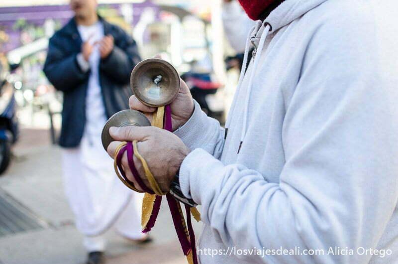 hare krishna tocando dos platillos pequeños que sostiene con los dedos