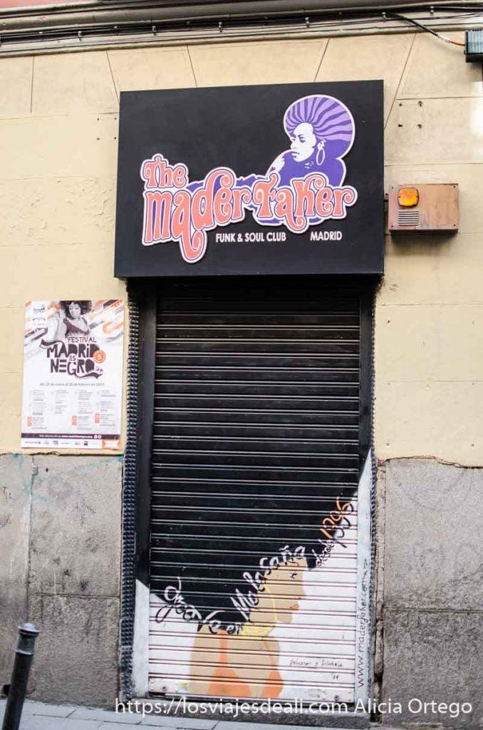 puerta del local Mad Facker de Malasaña con dibujo de cabeza de mujer con gran pelo rizado negro