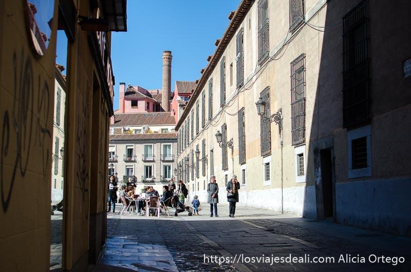 calle de malasaña que desemboca en una plaza con edificios del madrid de los austrias