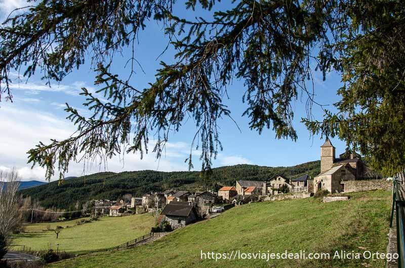 pueblo de aísa con su torre campanario y prados alrededor en día soleado