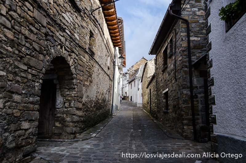 calle con casas de piedra y al fondo blancas