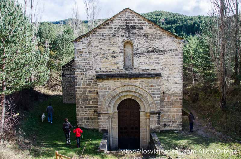 ermita románica entre árboles y varios caminantes alrededor