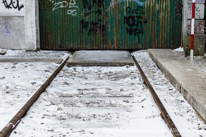 final de vía vieja con nieve y al fondo puerta de chapa verde